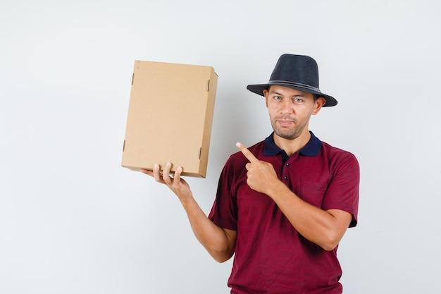 赤いシャツ、黒い帽子の箱を指して、安心して見える若い男性。正面図。
