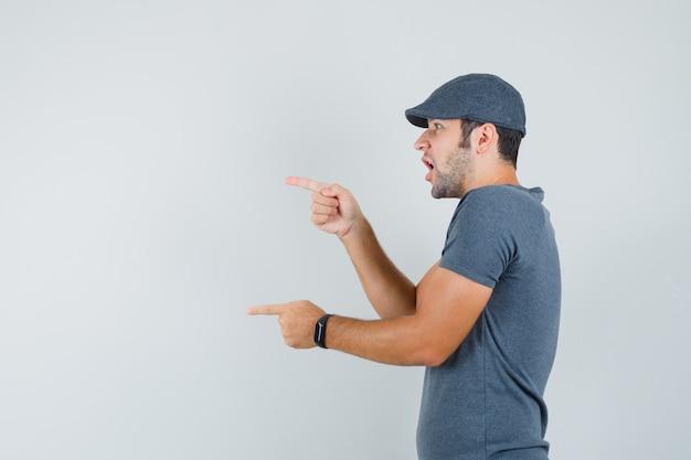회색 티셔츠, 모자에 그의 앞을 가리키고 놀란 젊은 남성. .