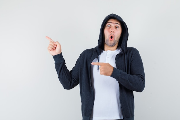 Tシャツ、ジャケットで左側を指して驚いて見える若い男性。正面図。