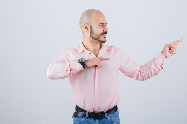 若い男性はシャツ、ジーンズで右側を指して、陽気に見えます。正面図。