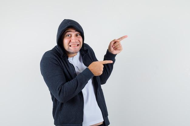 若い男性がtシャツ、ジャケットで右側を指して、陽気に見えます。正面図。