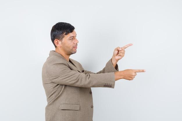 灰色がかった茶色のジャケット、黒のシャツで横を指して、集中して見える若い男性。