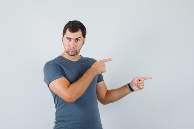 灰色のtシャツで横を指して物思いにふける若い男性