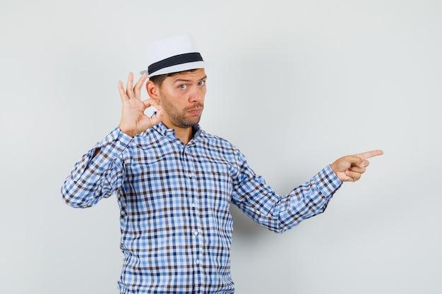 チェックシャツでokジェスチャーを示しながら横を指している若い男性