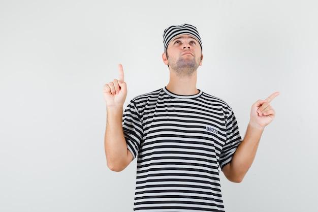 젊은 남성 가리키는 옆으로 t- 셔츠, 모자 및 희망 찾고. 전면보기.