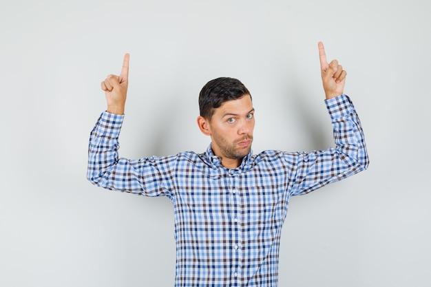 Молодой мужчина указывает вверх в клетчатой рубашке и выглядит серьезно