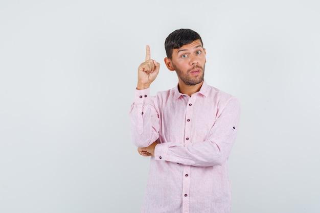 Молодой мужчина, указывая вверх в розовой рубашке и глядя внимательно, вид спереди.