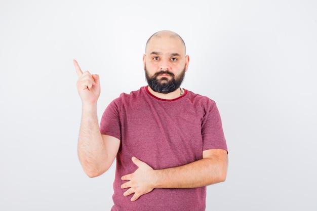 Молодой мужчина, указывая вверх в розовой футболке и глядя сосредоточенно, вид спереди.