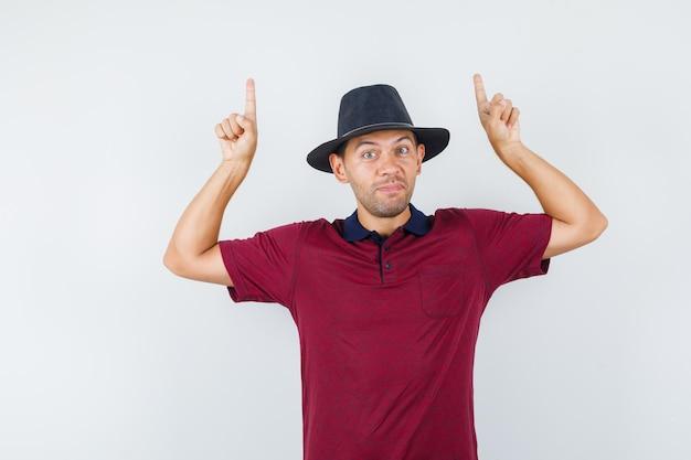 빨간 셔츠, 검은 모자 전면 보기를 가리키는 젊은 남성.