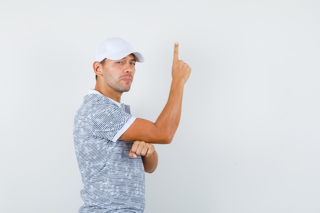Tシャツとキャップで上向きに気づいている若い男性