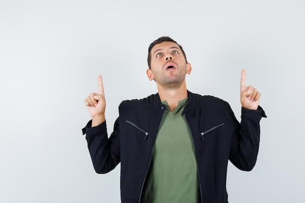 젊은 남성이 티셔츠, 재킷을 입고 희망적으로 보이는 전면 전망을 가리키고 있습니다.