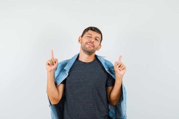 Молодой мужчина показывает вверх в куртке футболки и выглядит мирно