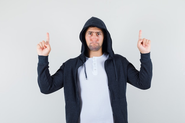 T- 셔츠, 재킷을 가리키는 심각한 찾고 젊은 남성. 전면보기.
