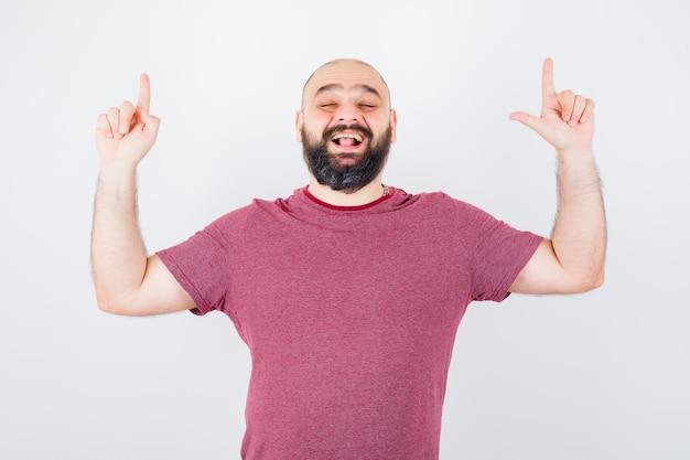 분홍색 티셔츠를 입고 웃고 즐거운 표정으로 가리키는 젊은 남성. 전면보기.