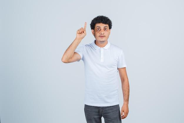 Giovane maschio rivolto verso l'alto in maglietta bianca, pantaloni e sembra sensato. vista frontale.