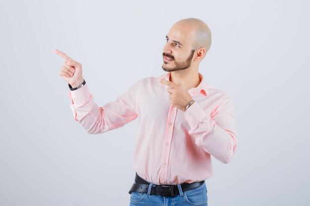 Giovane maschio che indica all'angolo superiore sinistro in camicia, jeans e sembra sicuro. vista frontale.