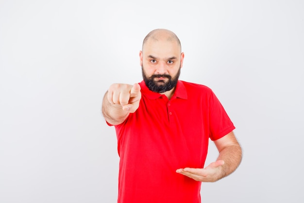 Giovane maschio in posa come tenere qualcosa mentre si punta la telecamera in camicia rossa, vista frontale.
