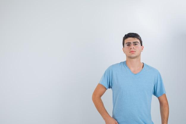 젊은 남성 티셔츠에 카메라를보고 심각한, 전면보기를 보면서 포즈.