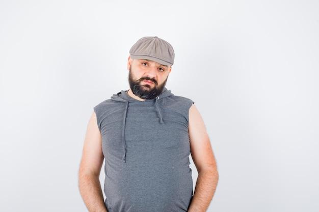 민소매 후드티를 입고 모자를 쓰고 자신감을 보이는 젊은 남성이 포즈를 취하고 있습니다. 전면보기.