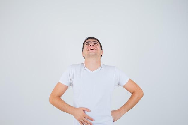若い男性がtシャツを着て腰に手を当ててポーズをとって、うれしそうな正面図を探しています。