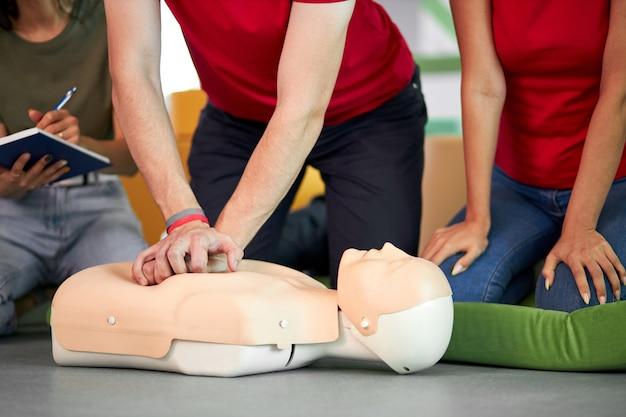 사람들 앞에서 마네킹에 심폐 소생술 응급 처치를 연습하는 젊은 남성