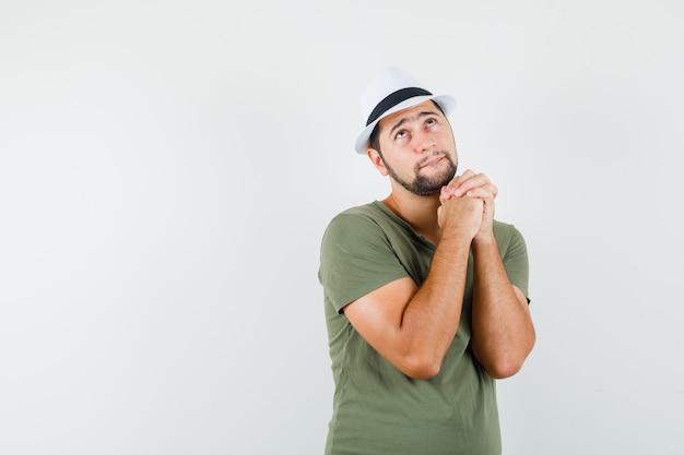 緑のtシャツと帽子を握りしめて祈って、希望に満ちた若い男性