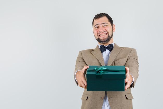 Молодой мужчина представляет подарочную коробку в костюме и выглядит счастливым. передний план.