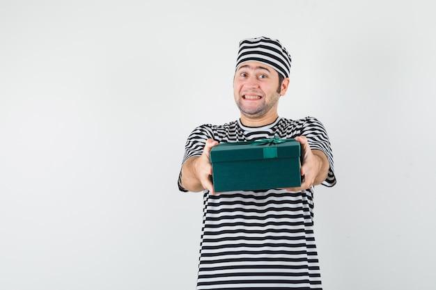 T- 셔츠, 모자에 선물 상자를 제시 하 고 기쁜 찾고 젊은 남성. 전면보기.