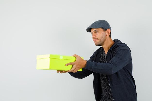 Giovane maschio che presenta confezione regalo in t-shirt, giacca, berretto e sembra gentile. vista frontale.