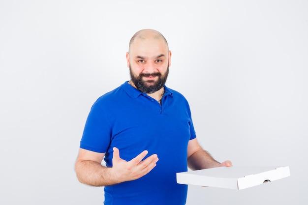 젊은 남성이 티셔츠에 피자 상자를 제시하고 쾌활하고 앞모습을 보고 있습니다.