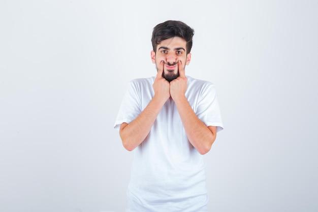 若い男性がtシャツの頬に指を押して、かわいく見えます。正面図。