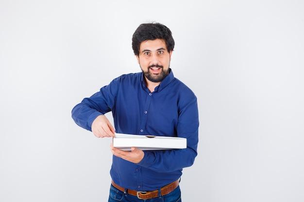 Giovane maschio che finge di aprire la scatola della pizza in camicia, jeans e sembra felice, vista frontale.