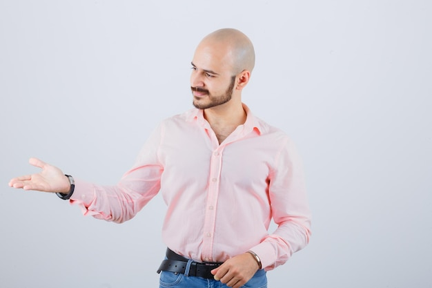 Young male pretending to show something in shirt, jeans and looking happy. front view.