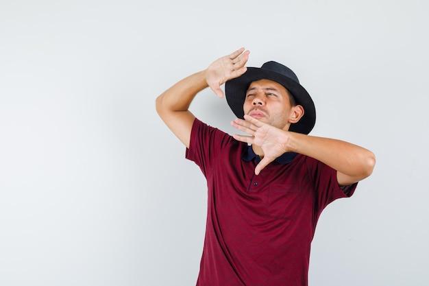 Giovane maschio che impedisce la pelle del viso dal sole splendente in maglietta, cappello e sembra a disagio. vista frontale.