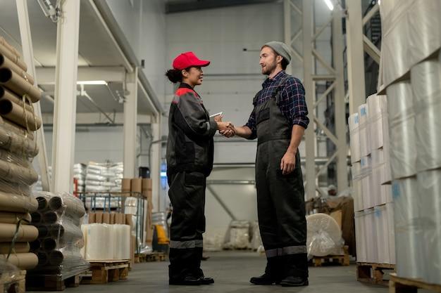 Молодой мужчина-профессионал в комбинезоне и клетчатой рубашке, пожимая руку своей коллеге-женщины с цифровым планшетом во время работы на складе