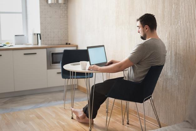 ホーム デスクに座ってコンピューターを使用する若い男性の専門家。自宅で働く忙しいフリーランサー。
