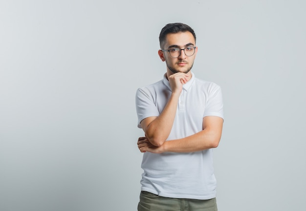 Молодой мужчина подпирает подбородок рукой в белой футболке, брюках и выглядит задумчиво