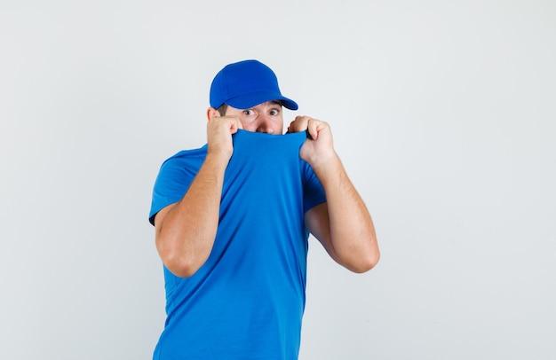 파란색 티셔츠와 모자에 얼굴에 칼라를 당기고 무서워하는 젊은 남성