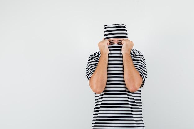Tシャツ、帽子、怖い顔、正面図で顔に襟を引っ張る若い男性。