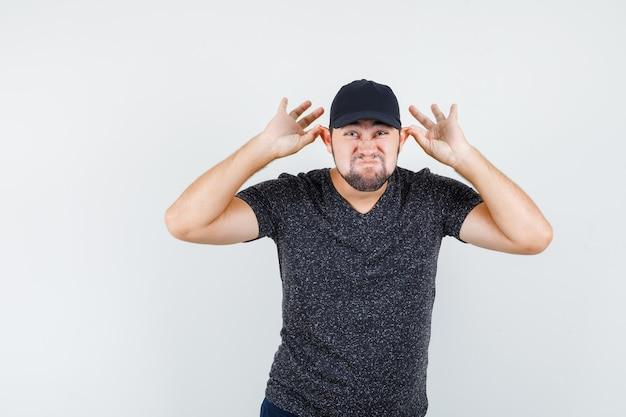 Молодой мужчина тянет за уши пальцами в черной футболке и кепке и выглядит забавно