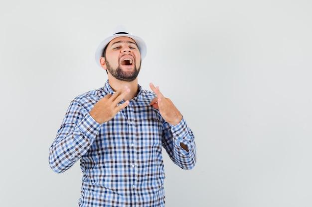 チェックシャツ、帽子を指で引っ張って自信を持って見える若い男性。正面図。