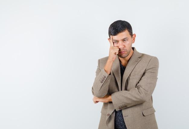 若い男性は灰色がかった茶色のジャケットを着て彼の顔に手を置き、思慮深く見えます。正面図。あなたのテキストのための空きスペース