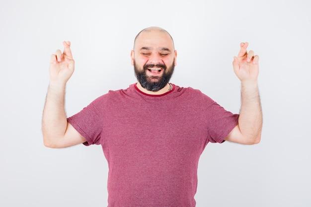 분홍색 티셔츠를 입고 웃고 즐거워 보이는 젊은 남성이 손가락을 교차시켰습니다. 전면보기.