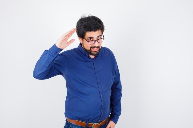 ロイヤルブルーのシャツ、メガネで挨拶のために手を上げる若い男性と楽観的な外観、正面図。