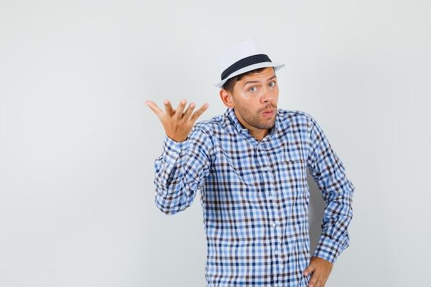 Giovane maschio alzando la mano nel gesto interrogativo in camicia controllata