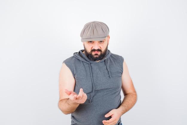 Giovane maschio alzando la mano in interrogatorio posa in felpa con cappuccio senza maniche, berretto e guardando serio, vista frontale.