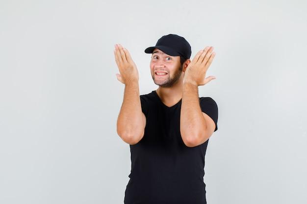 Giovane maschio alzando le mani in maglietta nera, berretto e guardando allegro.