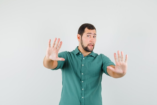 Young male raising hands to defend himself in green shirt and looking scared , front view.
