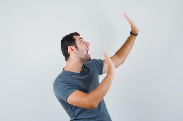Giovane maschio alzando le mani per difendersi in maglietta grigia e guardando agitato