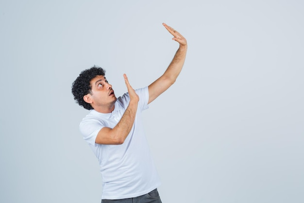 Young male raising hands to defend himself in white t-shirt, pants and looking scared. front view.